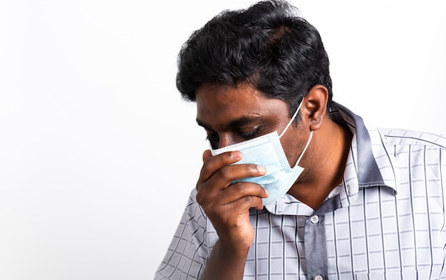 Черный человек, носящий хирургическую гигиеническую защитную маску для лица против коронавируса, он чихает