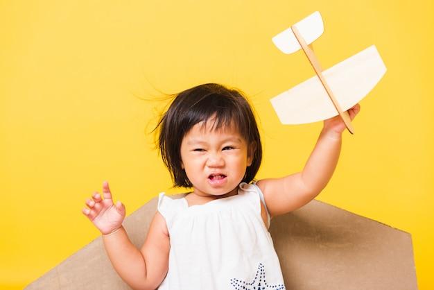 子供の小さな女の子の笑顔がおもちゃの段ボールの飛行機の翼を持つパイロットの帽子遊び