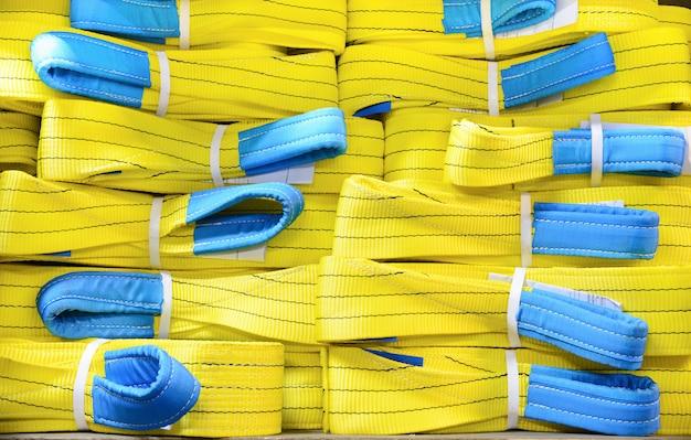 Желтые нейлоновые мягкие подъемные стропы укладываются в стопки.