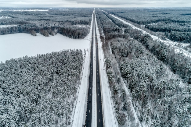 冬の森を通る高速道路。道は地平線に向かいます。