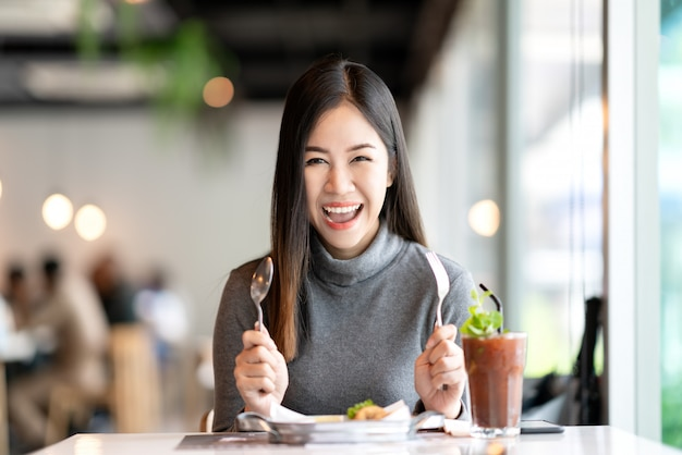 フォークとスプーンを保持している若い魅力的なアジア女性
