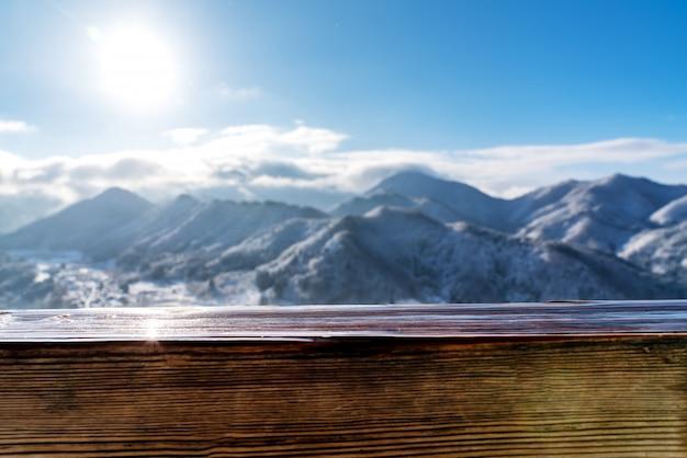 ぼやけている雪の山の景色の前に空の木の板トップテーブル