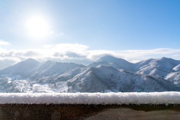 Пустой деревянный стол сверху перед размытым снежным горным видом