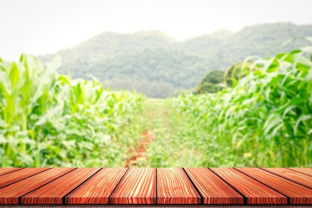 Пустой стол на деревянной доске перед размытым фоном кукурузного поля