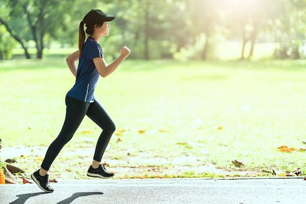 公共の自然都市で走っている若い魅力的な幸せなアジアランナー女性