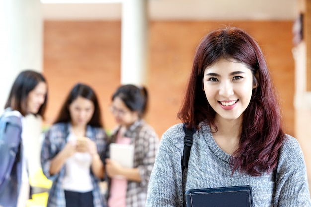 Молодой счастливый привлекательный азиатский студент усмехаясь к камере
