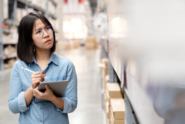率直な若い不幸なアジアの女性が倉庫で混乱しています。