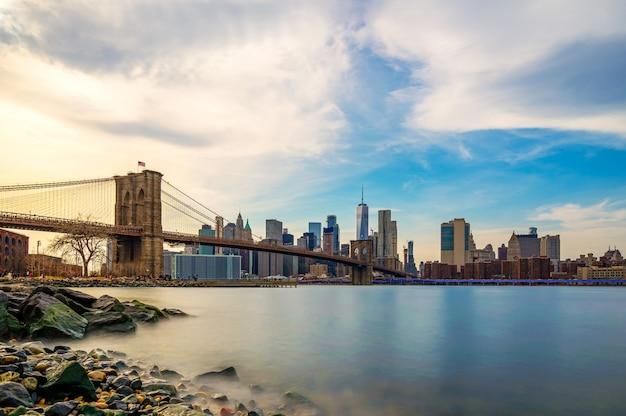 Красивый смысл бруклинского моста и нижний манхэттен нью-йорка в сумерках вечером. центр города нижнего манхэттена нью-йорка и гладкой реки гудзон с закат светом.