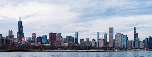 夕方夕暮れの曇りの青い空の夕日のシカゴのスカイラインのビジネス地区の美しい景色。ミシガン湖と都市の海岸線のパノラマビュー。アメリカ、シカゴの有名なアトラクション。