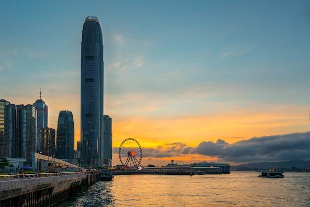 Остров гонконг с заходом солнца и предпосылкой сумрака. пейзаж и городской пейзаж вечернего голубого и оранжевого неба