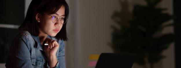 Откровенный молодой привлекательной азиатской студентки сидя на столе при умное цифровое устройство смотря тетрадь работая на поздней ночи с концепцией исследования проекта, график-дизайнера или программиста.
