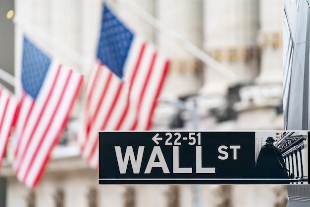 ニューヨーク市の金融経済とアメリカ国旗の背景を持つビジネス地区のウォール街サイン。株式市場の取引および交換ゾーン。