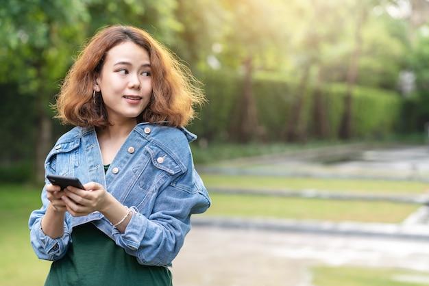 トレンディな巻き毛のブルネットの髪のスタイリッシュな女性デザイナーやインフルエンサーが広告のために側にいるスマートフォンを使用して家の外の庭に立っている若い幸せな魅力的なアジアの率直です。