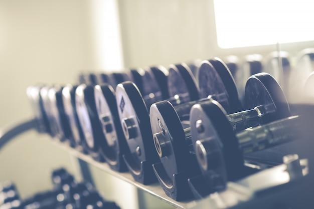 ジム/スポーツクラブのラックの金属ダンベルの列。ウェイトトレーニング機器。