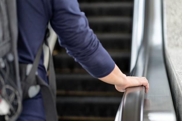 ハンドレールを持っているアジアの旅行者の男が階段を上がる