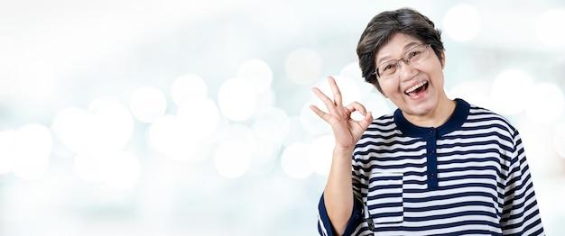 幸せな上級アジアの女性のジェスチャーや手を見せて肖像画の大丈夫