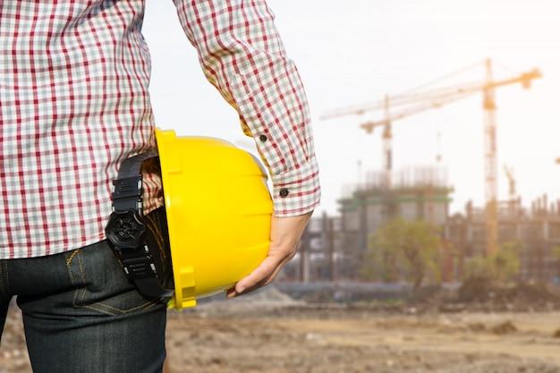 サイトの背景に建物を持つ黄色の安全ヘルメットを保持している手のエンジニアの労働者。