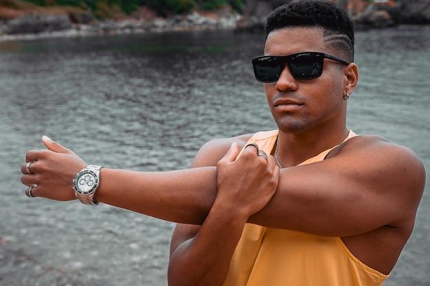若い男と海と岩を背景にワークアウトのサングラスをかけた男