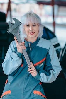 ガレージでレンチでポーズをとって自動車整備士として魅力的な若い女性