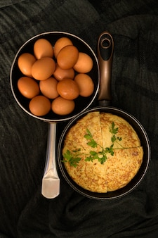 Два ростера в разные стороны со свежими яйцами и омлетом, разделенным на четыре части