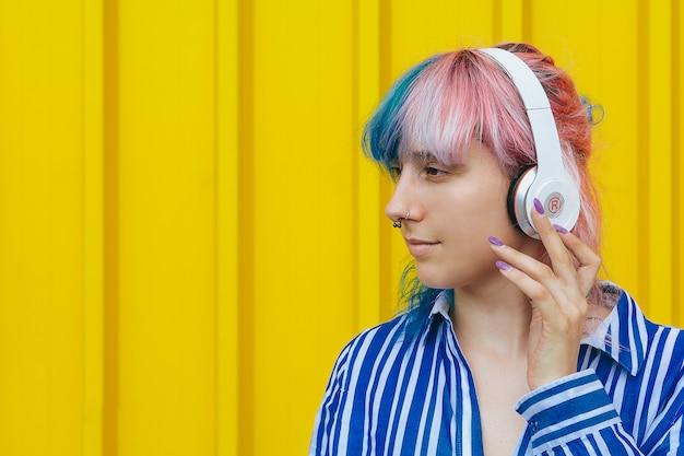若い女の子が大きな白いヘッドフォンでお気に入りの音楽を聴く