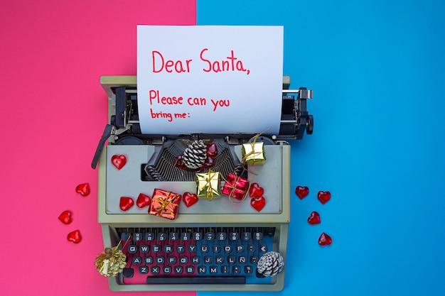 「親愛なるサンタ」の碑文とギフトボックスとモミの枝を持つタイプライター
