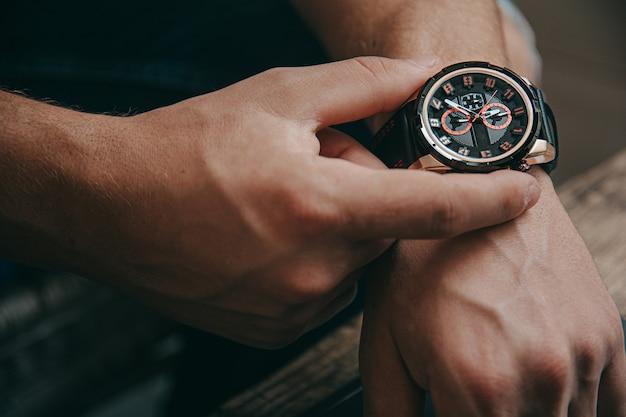 Деловой человек проверяет время на своих роскошных часах