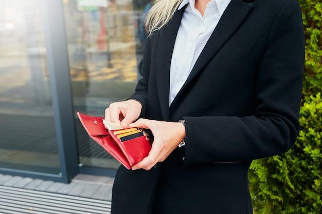 女性の手でお金とクレジットカード。開いている財布を持つ少女。
