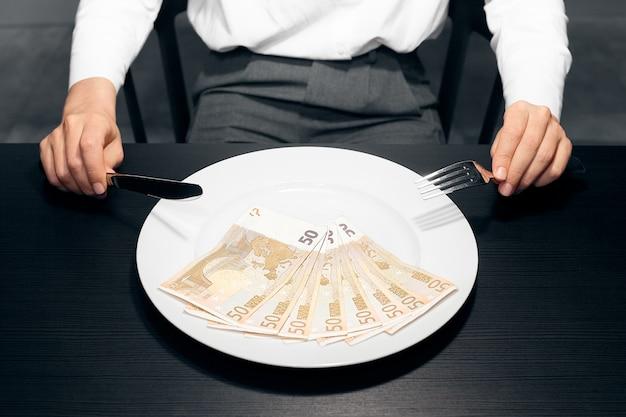 Деньги. тарелка евро банкноты и женские руки.