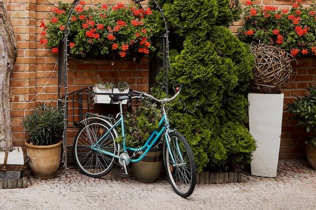 レンガの壁にビンテージ自転車、花、レトロなスタイリッシュな旧市街、青いレトロな自転車で。