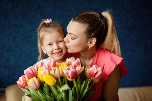 幸せな女性の日!子供はお母さんを祝福し、彼女のチューリップの花を与えます。家族の休日と一体感。