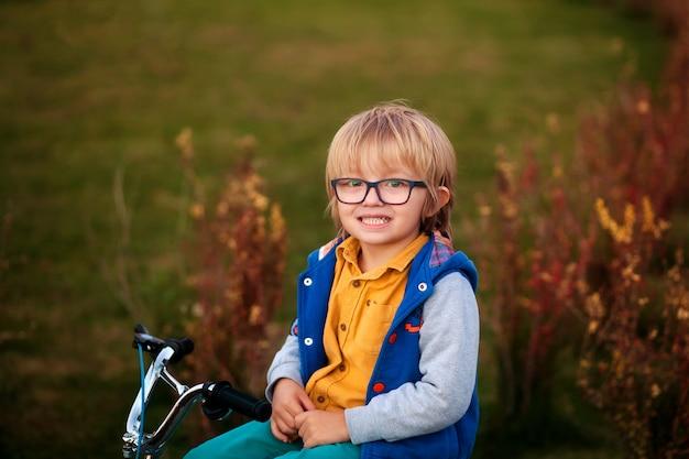 秋の公園でサイクリング幸せな少年
