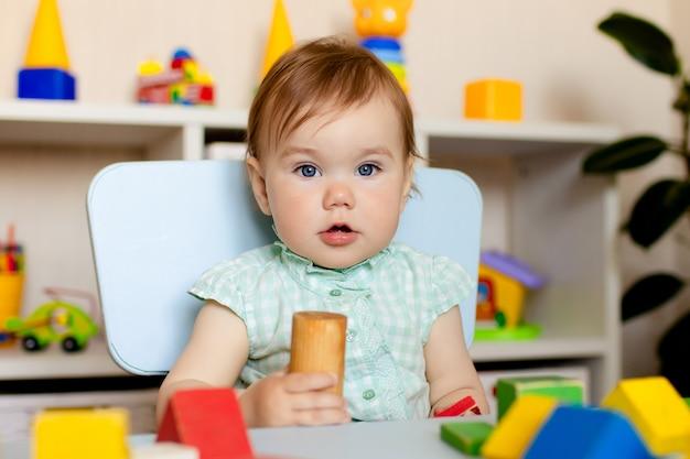 Счастливая маленькая девочка играет с игрушками на дому