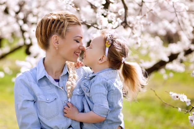 幸せな家族、母と娘の春の自然、フラワーガーデンの肖像画