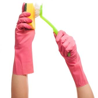 スポンジとブラシを保持しているピンクの手袋で手