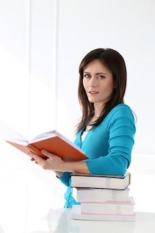 Красивая девушка с синей футболкой и книгами