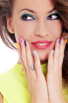 美しい少女は、色の指で彼女の顔に触れる