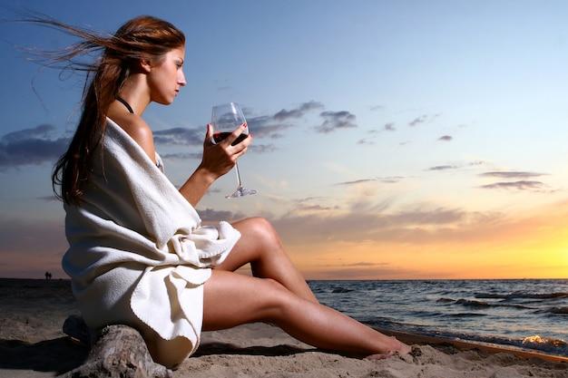 ビーチでワインを飲む美しい若い女性