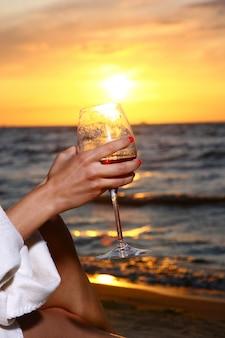 美しい若い女性はビーチでワインを飲む