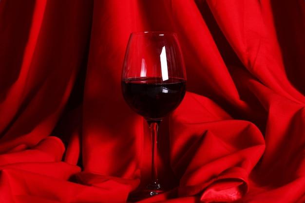 Стакан красного вина на красной ткани