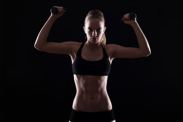Сексуальная женщина делает упражнения с гантелями
