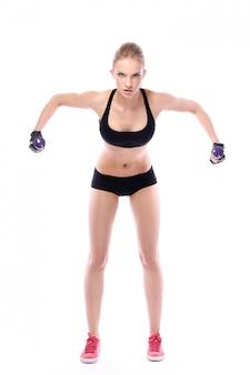 Красивая женщина делает упражнения с гантелями