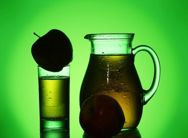 緑のスポットライトで新鮮で冷たいリンゴジュース