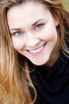 Молодая улыбающаяся девушка с голубыми глазами