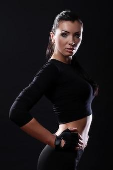 黒の背景の上の美しいフィットネス女の子