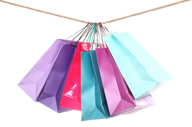 ロープでぶら下がっているカラフルなショッピングバッグ