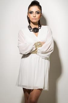 Красивая женщина позирует в белом платье