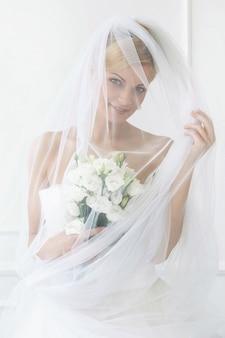 Красивая невеста с вуалью и букетом