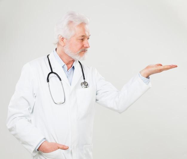 ハンサムな高齢医師が何かを保持します
