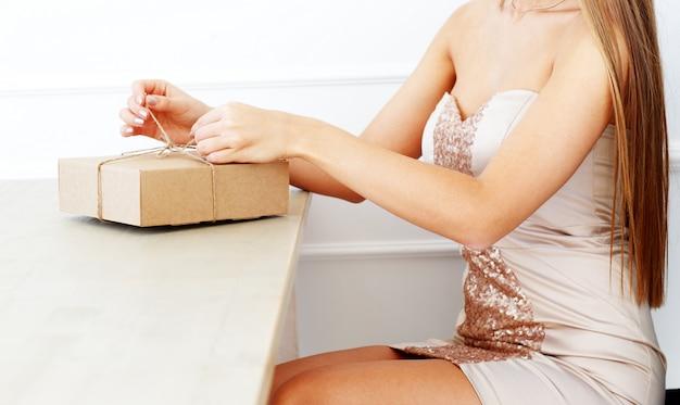 エレガントな女性がパッケージを開きます